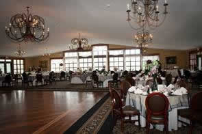 Ridgecrest dining hall with chandeliers and table settings in white