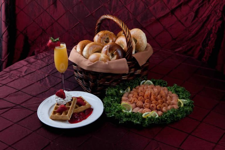 A basket with bagels, a plate with strawberry topped waffles, and a plate of deli meat