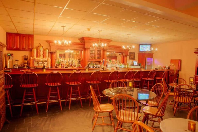 Photo of the bar with wooden chairs, cabinetry and tables in the room