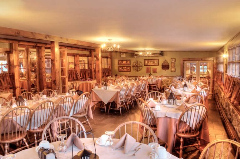 The Stroudsmoor Inn Stone room is a large dining area with numerous tables covered in rose table clothes