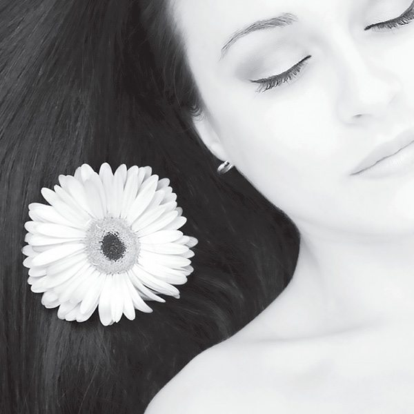 Black and white close up of a woman's face. Her hair is spread out next to her with a daisy on top.