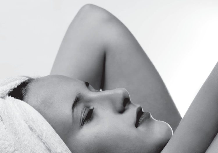 Black and white close up of a woman in profile with her hair in a towel
