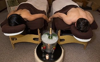 A couple is face down on two massage beds. They are holding hands.