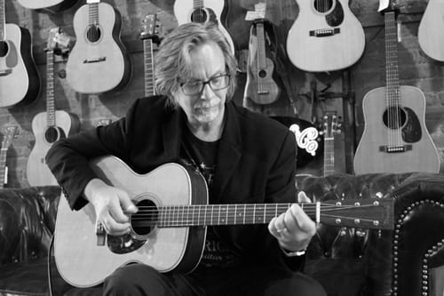 An older man with full hair and black rimmed glasses is sitting in a chair playing an acoustic guitar. There are numerous guitars hanging on the wall in the back.