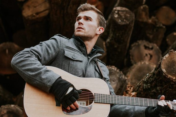 A male with short blond hair leans against a pile of logs while holding a guitar