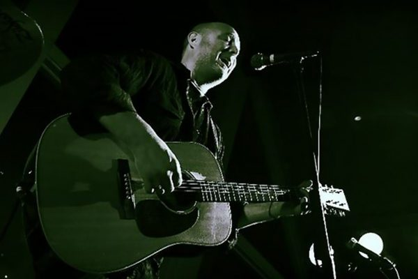 A man playing guitar sings patiently into a microphone