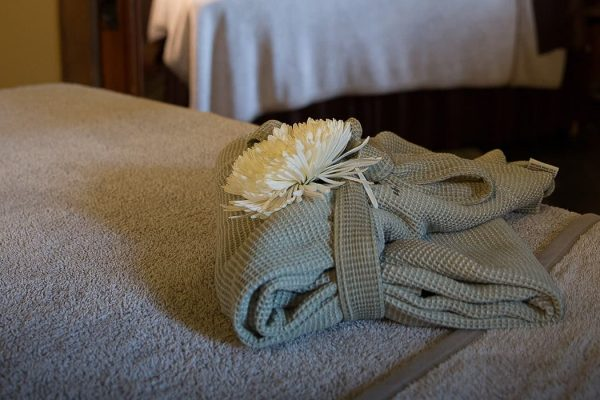 A bathrobe folded gingerly on a bed with a flower on top.