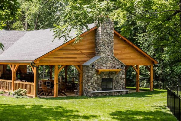 Stroudsmoor Pavilion with wood siding and stone fireplace, the lawn is lush green