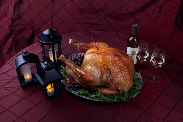 A whole roasted chicken on a platter with fruit, lanterns are to the left and wine glasses to the right
